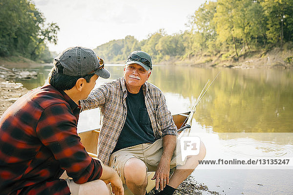 Male friends talking while sitting on boat by lake
