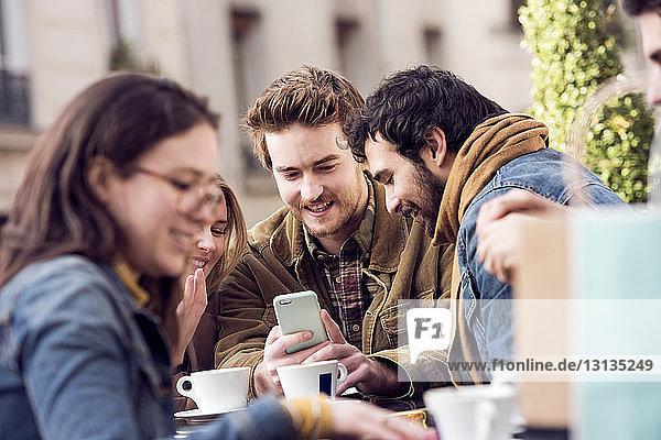 Glückliche Freunde benutzen gemeinsam ein Smartphone im Straßencafé