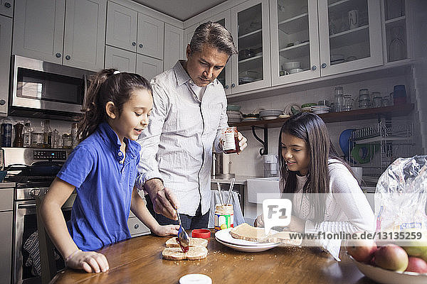 Girls looking at father applying preserves on bread at table