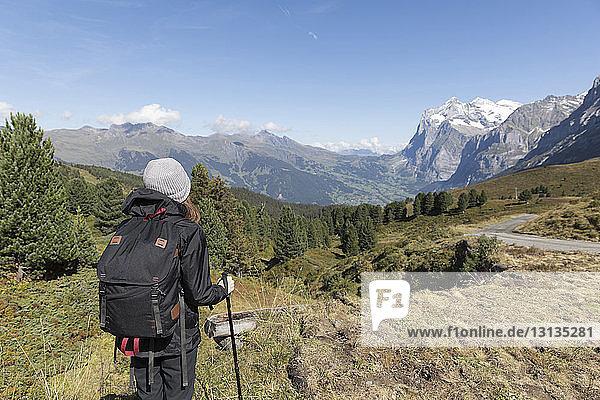 Rückansicht einer auf dem Berg stehenden Wanderin