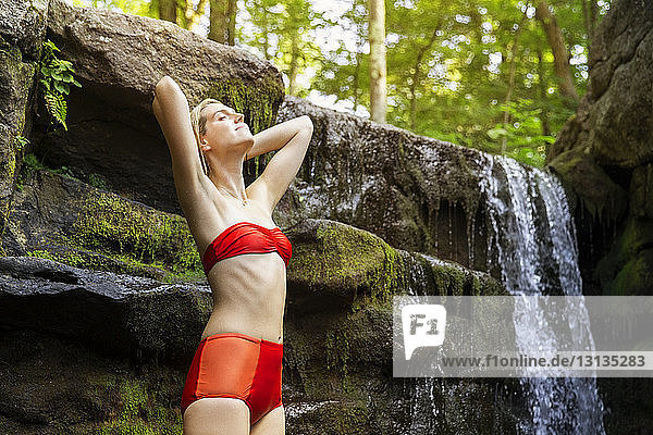Sensuous woman in red bikini standing with hands behind head by waterfall