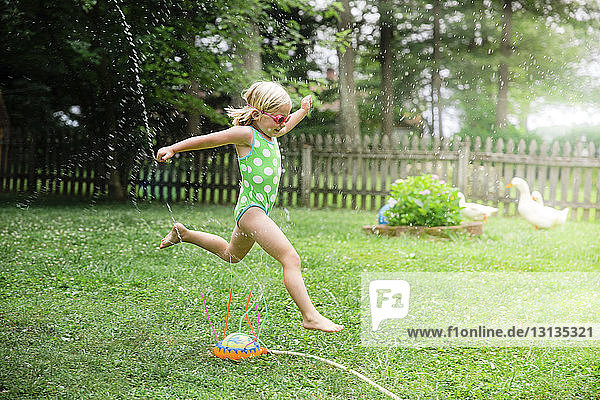 Side view of girl in swimwear running over sprinklers at yard