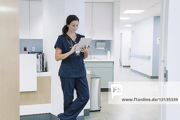 Ärztin  die einen Tablet-Computer benutzt  während sie sich im Krankenhaus an eine architektonische Säule lehnt