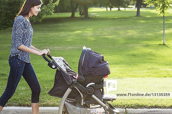 Seitenansicht einer lächelnden Frau mit Kinderwagen auf der Straße