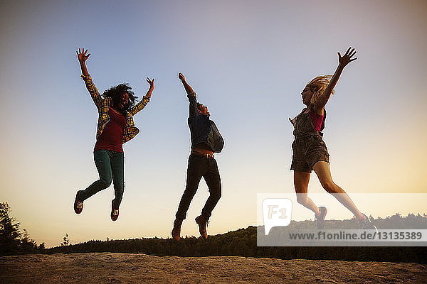 Friends jumping on rock against clear sky during dusk