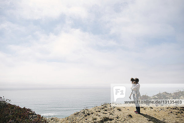 Woman carrying daughter while standing on cliff by sea against sky