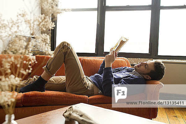 Man reading book while lying on sofa at home
