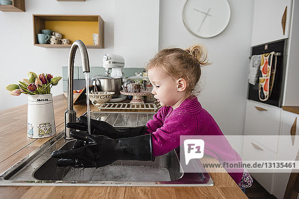 Girl wearing gloves washing hands in kitchen sink