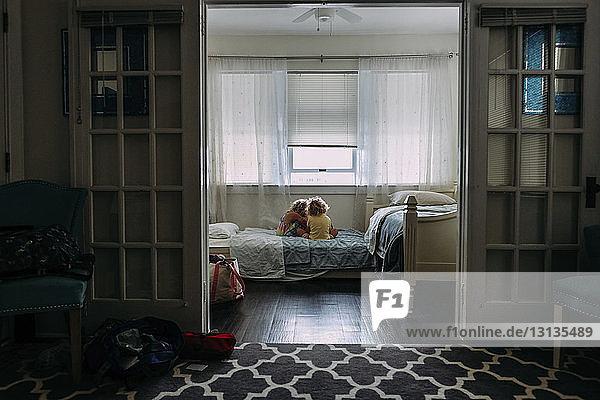 Schwestern sitzen auf dem Bett gegen das Fenster durch die Tür