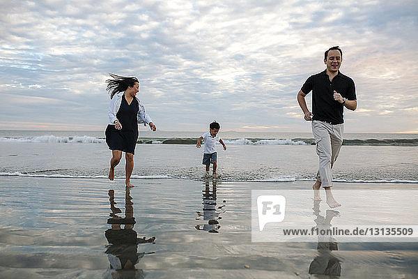 Glückliche Eltern mit Sohn rennen bei Sonnenuntergang am Strand gegen bewölkten Himmel
