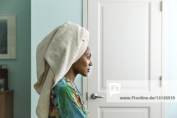 Seitenansicht Frau schaut weg  während sie ein Handtuch auf dem Kopf trägt