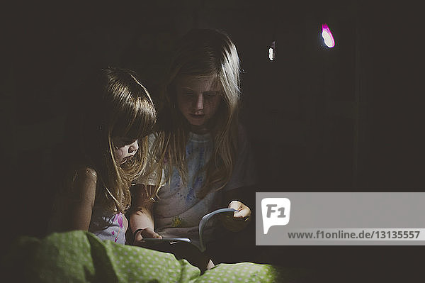 Girls reading book in dark room at home