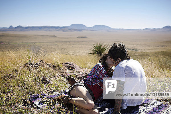 Couple kissing while sitting on field against clear sky