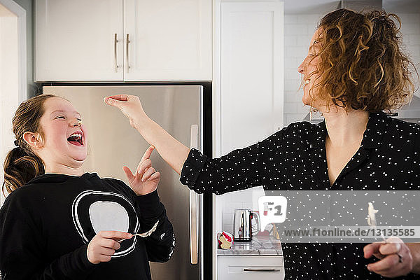 Playful mother with daughter standing by refrigerator in kitchen a home