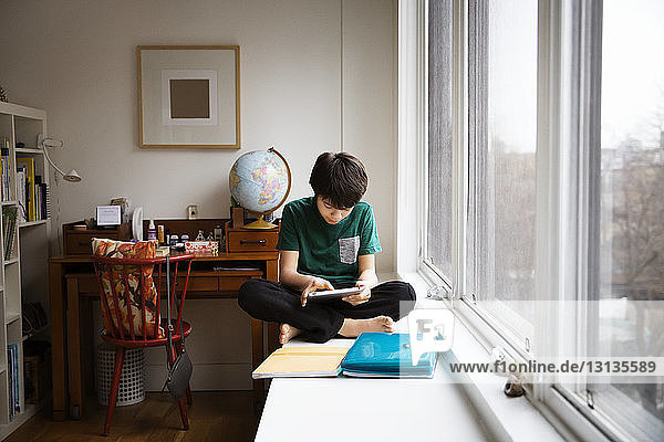 Boy using digital tablet while sitting on table by window at home