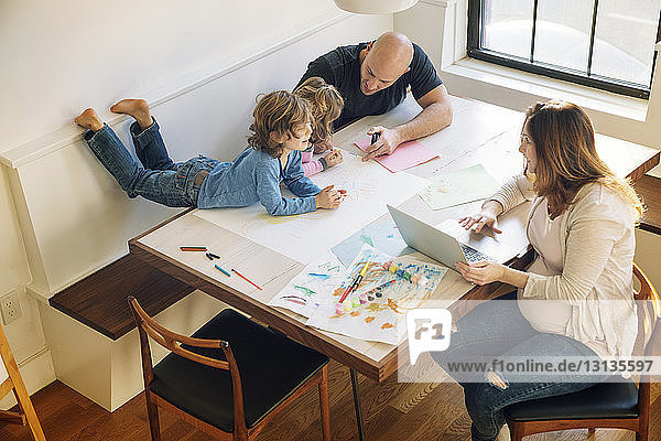 High angle view of father assisting children in drawing while woman using laptop at table