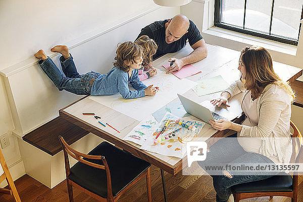 Hochwinkelansicht eines Vaters  der Kindern beim Zeichnen hilft  während die Frau am Tisch einen Laptop benutzt