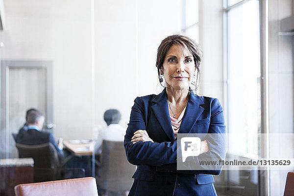Porträt einer selbstbewussten Geschäftsfrau mit verschränkten Armen im Amt