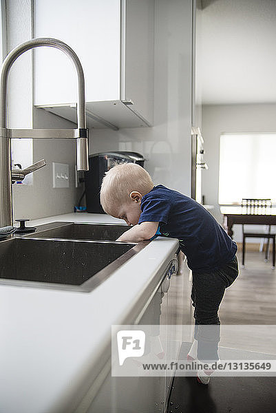 Side view of boy standing on stool by sink in kitchen