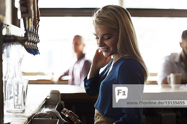 Lächelnde Besitzerin steht an der Theke eines Cafés