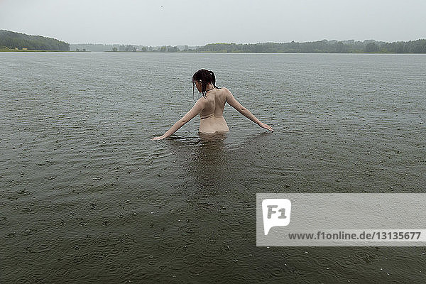 Rear view of shirtless young woman standing in lake during rainfall