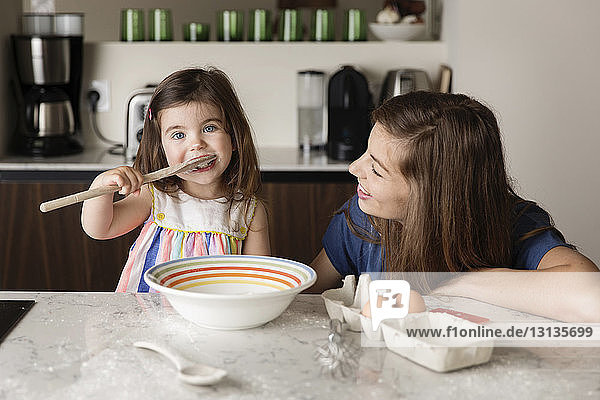 Mother looking at daughter tasting food in kitchen at home