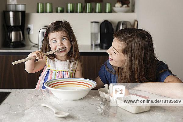 Mutter sieht Tochter bei der Verkostung von Essen in der heimischen Küche