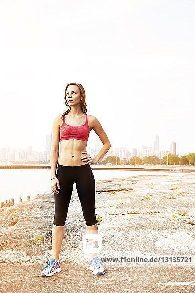 Weibliche Sportlerin schaut weg  während sie am Strand steht
