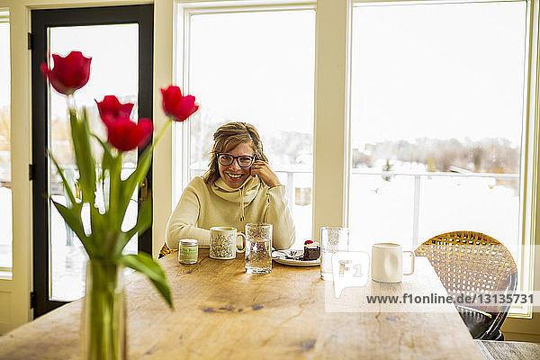 Porträt einer Frau  die zu Hause am Tisch sitzt