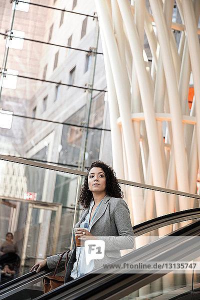 Nachdenkliche Geschäftsfrau hält Getränk in der Hand  während sie auf der Rolltreppe im Gebäude steht
