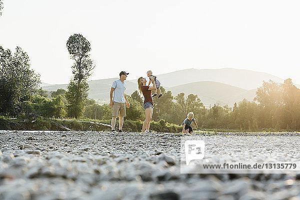 Familie genießt auf dem Feld gegen klaren Himmel bei Sonnenuntergang