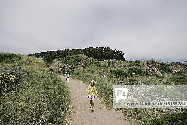 Girls walking on trail against sky