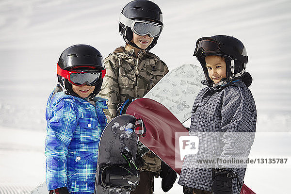 Siblings carrying snowboards while standing on snow covered field