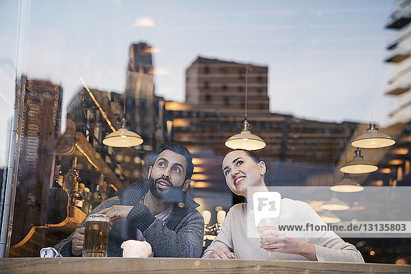 Couple enjoying drinks while looking away seen through restaurant window