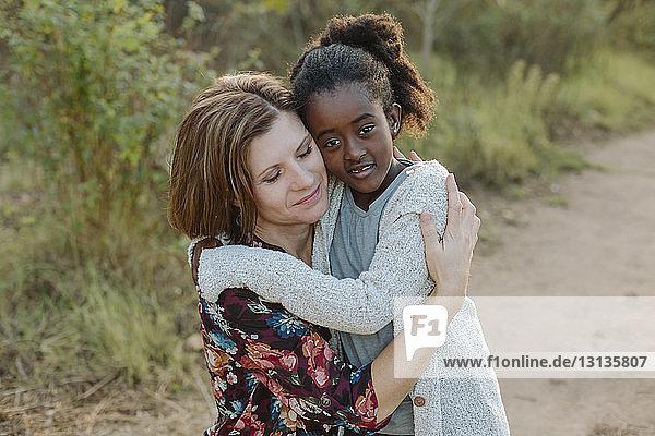 Porträt eines Mädchens  das seine Mutter im Park umarmt