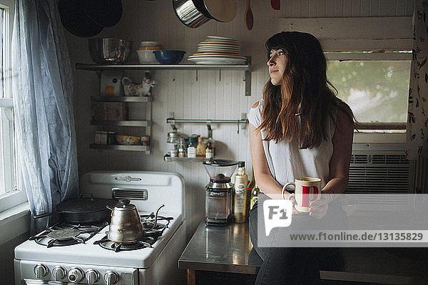 Nachdenkliche Frau hält Becher  während sie auf der Küchentheke sitzt