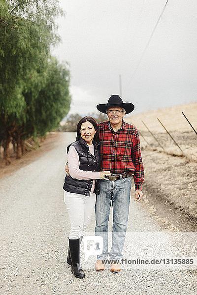 Porträt eines selbstbewussten Paares  das auf einem Feldweg steht