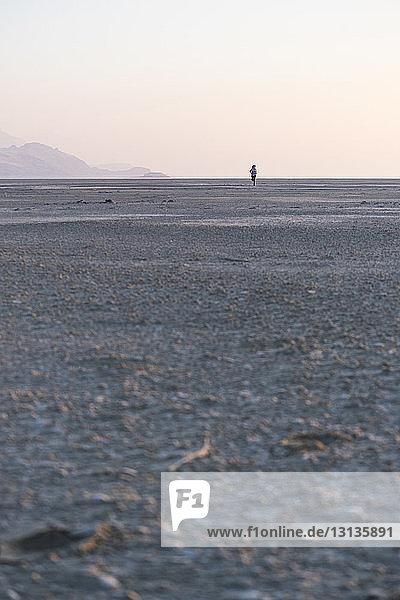 Fernblick einer Frau  die am Strand gegen den klaren Himmel bei Sonnenuntergang auf Sand läuft