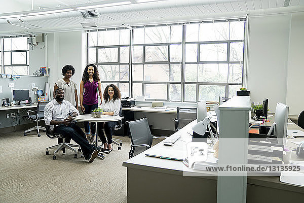 Portrait of smiling colleagues at table in office