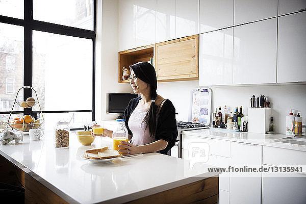 Glückliche Frau trinkt Saft in der Küche