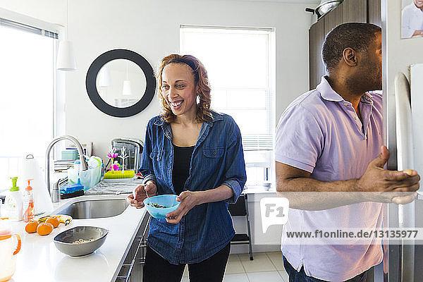 Glückliche Frau hält Schüssel  während der Mann in der Küche den Kühlschrank öffnet