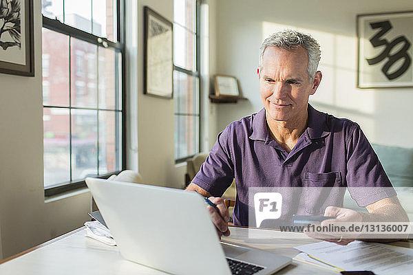 Reifer Mann benutzt Laptop-Computer  während er zu Hause Rechnungen bezahlt
