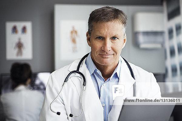 Porträt eines selbstbewussten männlichen Arztes mit Tablet-Computer in der Klinik