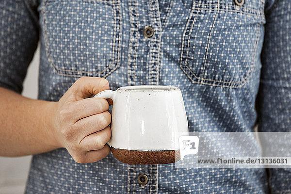 Midsection of woman holding earthenware mug