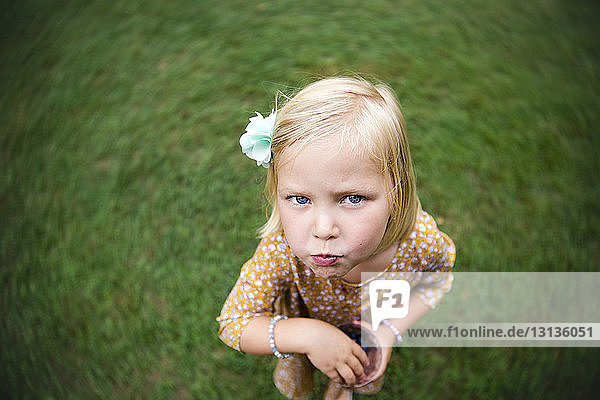 High angle portrait of girl eating blueberries while standing on grassy field