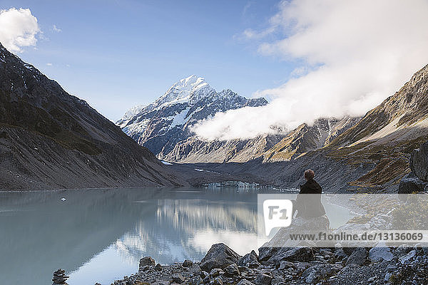 Rear view of hiker sitting at lakeshore against cloudy sky at Mt Cook National Park