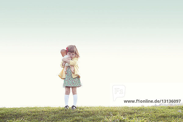 Cute girl embracing doll while standing on field against clear sky