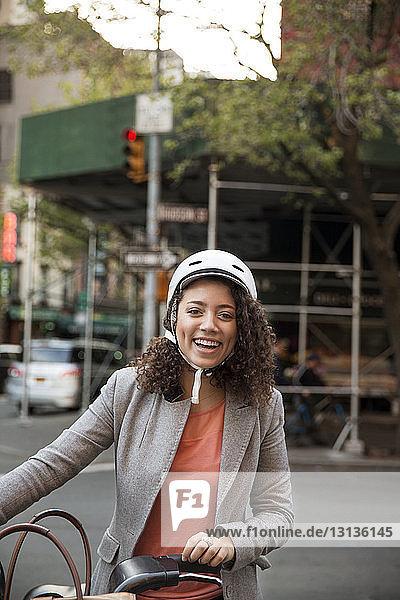 Porträt einer glücklichen Geschäftsfrau  die auf der Straße ein Fahrrad hält