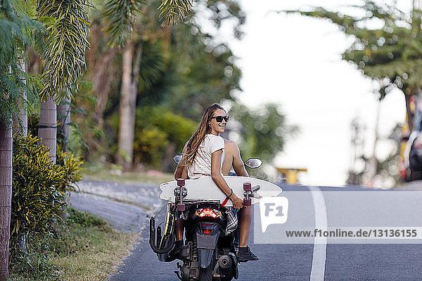 Rückansicht eines Freundes  der Motorrad fährt  während eine Frau ein Skateboard hält