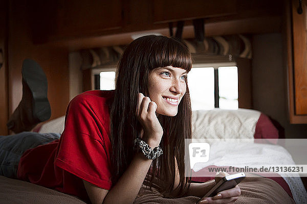 Thoughtful woman smiling while relaxing on bed in camper van